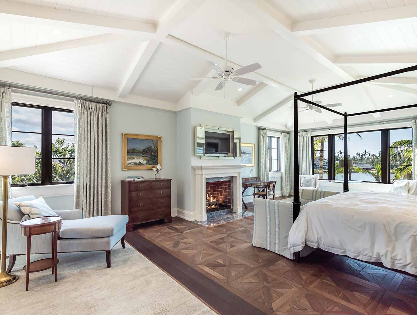 Master bedroom with fireplace and waterfront views in a Naples Florida, single family home. Designed by Kukk Architecture & Design Naples.